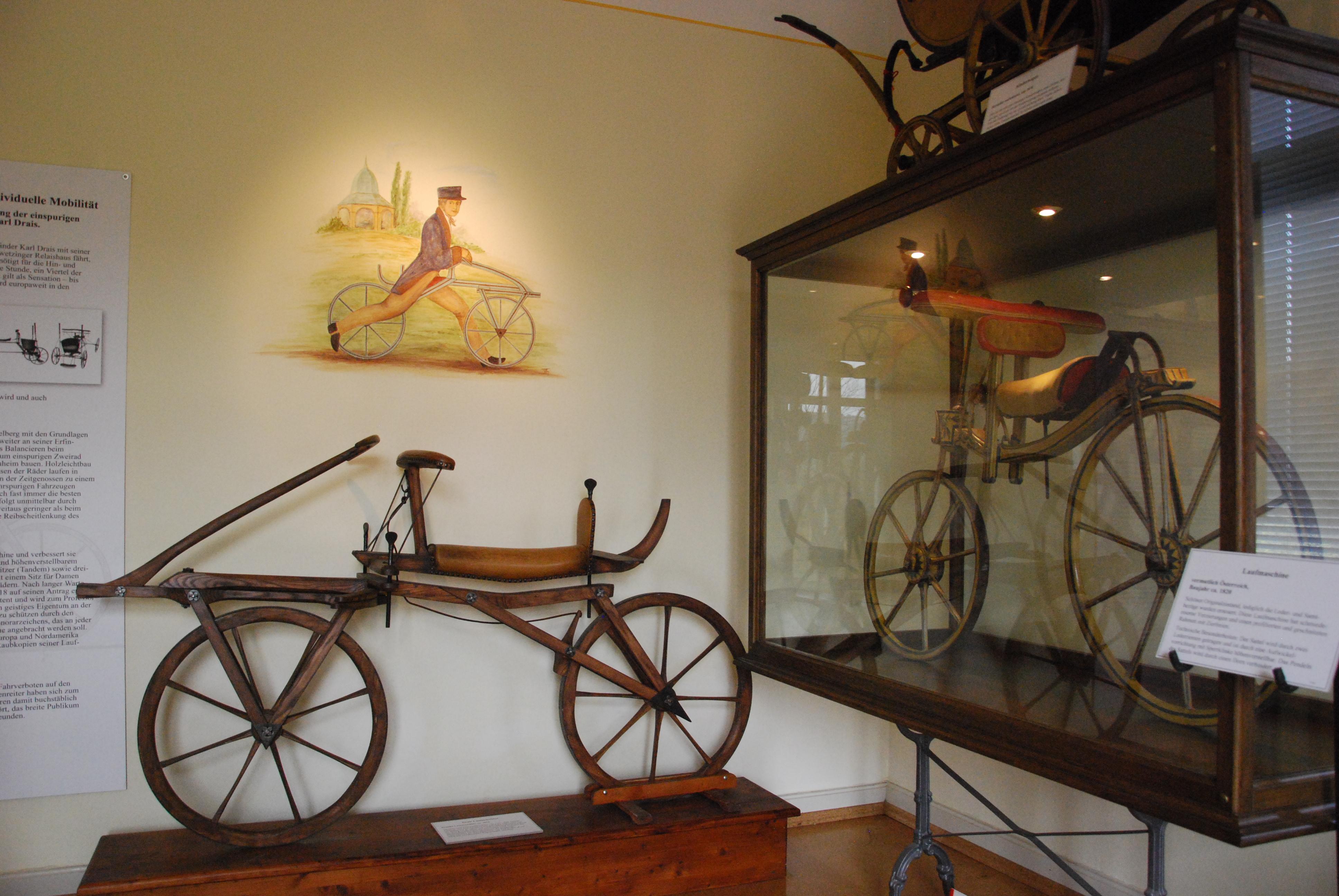 2 Laufmaschinen: Nachbau (ca. 1970) nach Drais, in der Vitrine ein österreichisches Modell um 1820